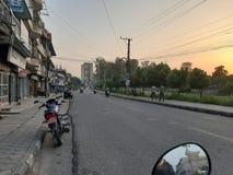 Puesta del sol alrededor de un camino ocupado Opini?n parqueada de la bici foto de archivo