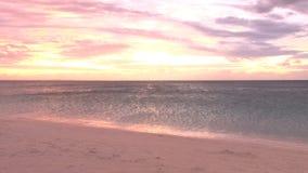 Puesta del sol amarilla y roja sobre la playa brillante del océano metrajes
