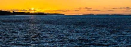 Puesta del sol anaranjada con agua azul profunda en Escandinavia Sol de medianoche con reflexiones Fotos de archivo