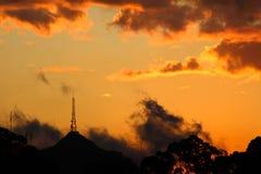 Puesta del sol anaranjada con lluvia y nubes de varios colores imagen de archivo