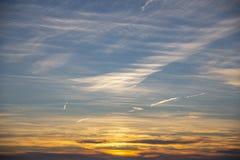 Puesta del sol anaranjada de oro y cielo azul profundo con poner en contraste plumoso blanco de las nubes imagen de archivo