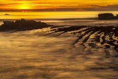 Puesta del sol anaranjada de oro y rocas Fotografía de archivo