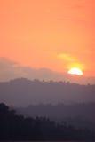 Puesta del sol anaranjada del cielo sobre una montaña fotografía de archivo libre de regalías