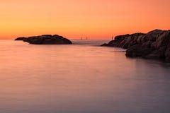 Puesta del sol anaranjada delante del mar Foto de archivo
