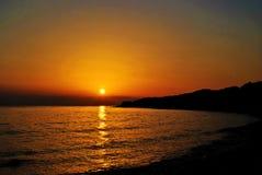 Puesta del sol anaranjada en el mar Foto de archivo libre de regalías