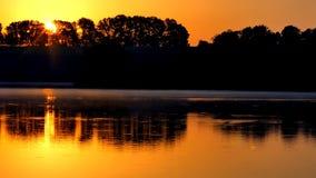 Puesta del sol anaranjada en el río Puesta del sol sobre el lago metrajes