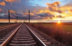 Puesta del sol anaranjada en nubes bajas sobre el ferrocarril imagen de archivo libre de regalías
