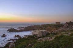 Puesta del sol anaranjada en un paisaje con la playa y la capilla foto de archivo