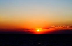 Puesta del sol anaranjada escénica en el cielo nublado de la belleza encima Foto de archivo