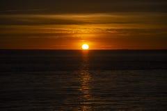 Puesta del sol anaranjada grande sobre el océano, Francia imagen de archivo
