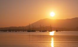 Puesta del sol anaranjada hermosa en el mar, silueta de la ciudad basque en la salida del sol en la costa, paisaje pacífico fotos de archivo