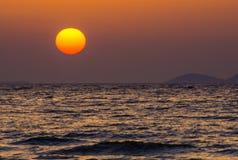 Puesta del sol anaranjada hermosa sobre el mar violeta Foto de archivo libre de regalías
