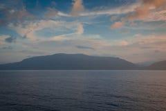 Puesta del sol anaranjada mientras que en el mar Fotografía de archivo