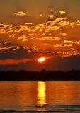 Puesta del sol anaranjada sobre el agua fotos de archivo