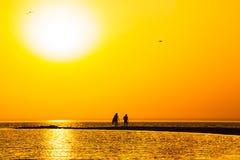 Puesta del sol anaranjada sobre el escupitajo de la arena en el mar Fotos de archivo libres de regalías