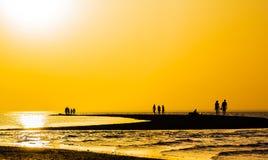 Puesta del sol anaranjada sobre el escupitajo de la arena en el mar Fotos de archivo