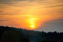 Puesta del sol anaranjada sobre las colinas y el bosque Fotos de archivo libres de regalías