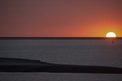 Puesta del sol anaranjada - Sun en horizonte se refractó en parte el primero plano anaranjado y negro profundo de la arena del rí Imágenes de archivo libres de regalías