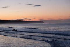 Puesta del sol anaranjada y azul hermosa sobre una playa Imágenes de archivo libres de regalías