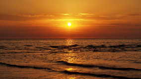 Puesta del sol anaranjada y nubes en el mar Imagen de archivo libre de regalías