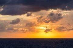 Puesta del sol anaranjada y púrpura en el mar Imágenes de archivo libres de regalías