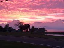 Puesta del sol anaranjada y rosada en el lago Imagen de archivo