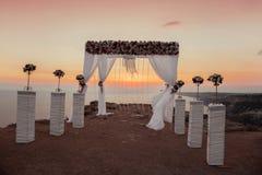 Puesta del sol Arco de la ceremonia de boda con arrangemen decorativos de las flores Imágenes de archivo libres de regalías