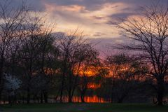Puesta del sol ardiente roja en paisaje ilustrado con los árboles que se reflejan en el río debajo del cielo de igualación azu fotografía de archivo libre de regalías