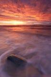 Puesta del sol ardiente sobre el mar Imágenes de archivo libres de regalías