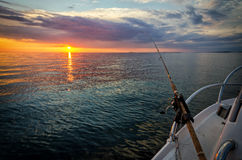 Puesta del sol asombrosa de la pesca en mar Imagen de archivo