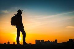 Puesta del sol asombrosa de observación de la silueta del viajero Imagen de archivo