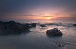 Puesta del sol asombrosa en el mar con la piedra imagen de archivo libre de regalías