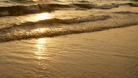 puesta del sol asombrosa 4K sobre la playa tropical la playa del océano agita en la playa en el tiempo de la puesta del sol, luz  almacen de video