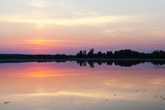 Puesta del sol asombrosa sobre el lago Reflexión colorida en el agua imagen de archivo