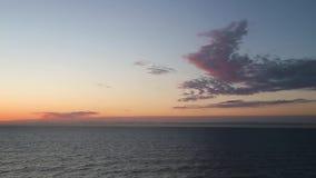 Puesta del sol asombrosa sobre la playa Las ondas de la playa del mar en la playa en el tiempo de la puesta del sol, luz del sol  almacen de metraje de vídeo