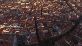 Puesta del sol asombrosa sobre los tejados de teja roja de la ciudad grande metrajes