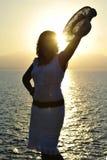 puesta del sol atractiva de la playa de la silueta de la mujer 40s delante del mar Imagen de archivo