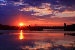 Puesta del sol azul y anaranjada hermosa en el agua con simetría de la cumulonimbus colorida de las nubes foto de archivo