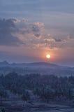 Puesta del sol azulada con las colinas y las palmas Fotografía de archivo libre de regalías