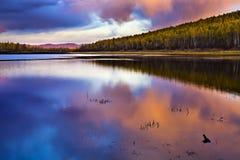 Puesta del sol bajo el lago y el bosque Imagenes de archivo