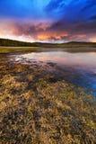 Puesta del sol bajo el lago y el bosque Fotografía de archivo