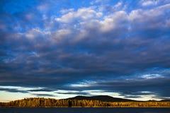 Puesta del sol bajo el lago y el bosque Imágenes de archivo libres de regalías