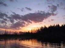 Puesta del sol bajo el lago y el bosque Fotografía de archivo libre de regalías