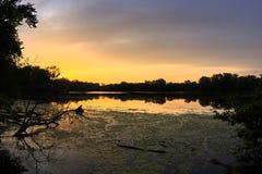 Puesta del sol brillante sobre laguna de agua dulce Fotos de archivo libres de regalías