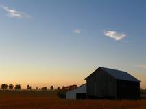 Puesta del sol caliente de la tarde del otoño con el granero y los fileds Fotos de archivo libres de regalías