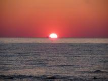 Puesta del sol caliente del mar con el buque de carga en el fondo Foto de archivo