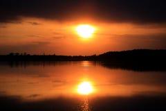 Puesta del sol caliente sobre el agua Foto de archivo libre de regalías