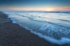 Puesta del sol caliente sobre la playa de la arena en Mar del Norte Foto de archivo libre de regalías