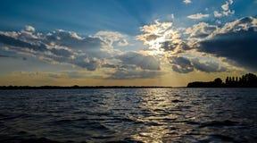 Puesta del sol caliente del verano sobre el río Danubio en el fondo de un cielo azul fotos de archivo libres de regalías