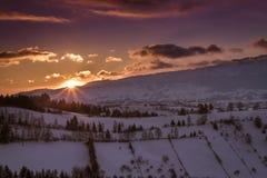 Puesta del sol caliente y colorida sobre el salvado, un pueblo de montaña de Transilvania, cubierta con nieve en invierno Imagenes de archivo